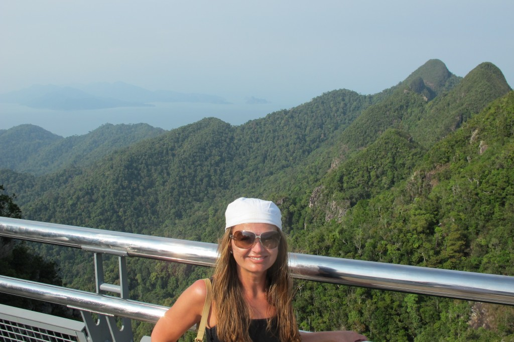 Jeg heter Mette, og jeg er Reiselykke. Her står jeg på toppen av Malaysia og i bakgrunnen ligger Thailands mange øyer